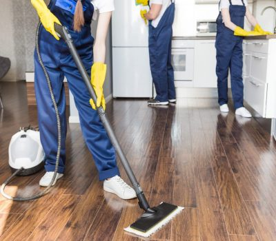 Cleaning service with professional equipment during work. professional kitchenette cleaning, sofa dry cleaning, window and floor washing. man and women in uniform, overalls and rubber gloves